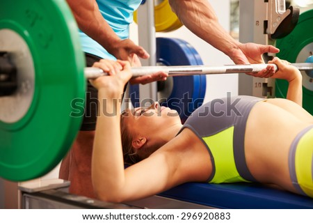 Woman bench pressing weights with assistance of trainer - stock photo