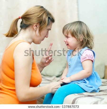 Woman berates crying baby at home - stock photo