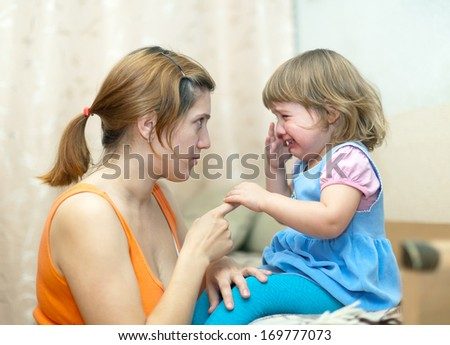 Woman berates crying baby in home - stock photo