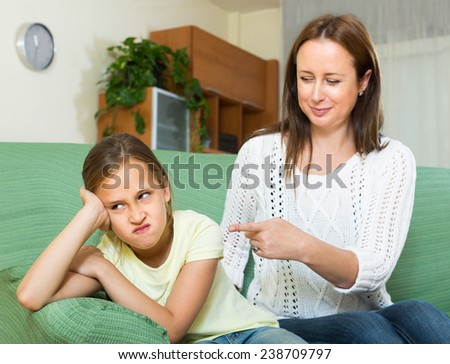 Woman berating offended daughter in home interior - stock photo