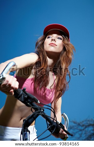 Woman biking under deep blue sky - stock photo