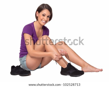 Woman binds her shoelaces - stock photo