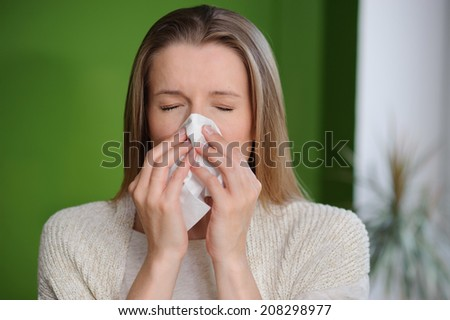 Woman blowing runny nose - Cold flu illness - stock photo
