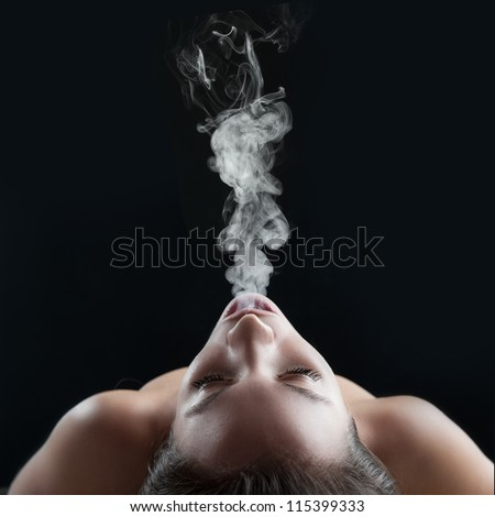 Woman blowing smoke against black background. Studio fashion photo. - stock photo