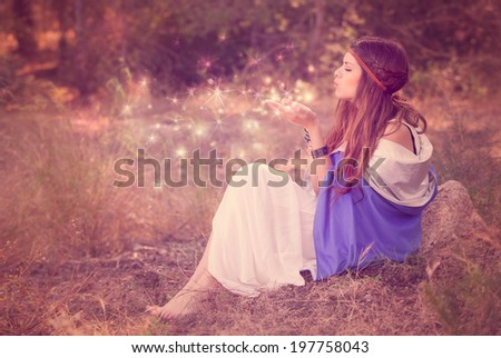woman blowing wishes in forest. fairy or elf - stock photo