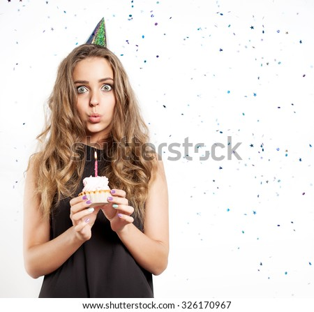 Woman blows out the candles on a birthday cake - stock photo