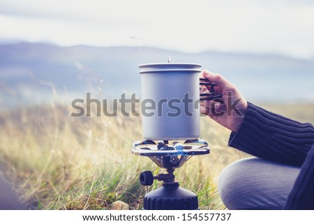 Woman boiling water on portable camping stove - stock photo