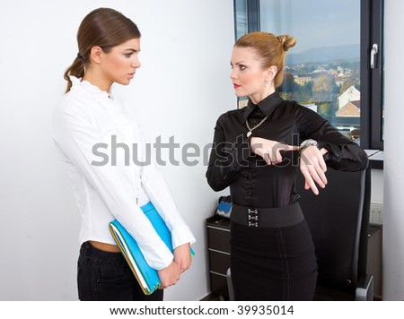 woman boss pointing at watch and showing time to her secretary - stock photo
