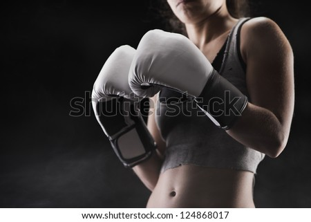 Woman boxer, focus on boxing glove, shallow deep of field - stock photo