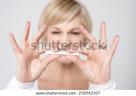Woman breaking cigarette, focus on cigarette. - stock photo