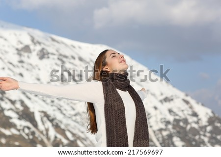 Woman breathing fresh air raising arms in winter with a snowy mountain in the background - stock photo
