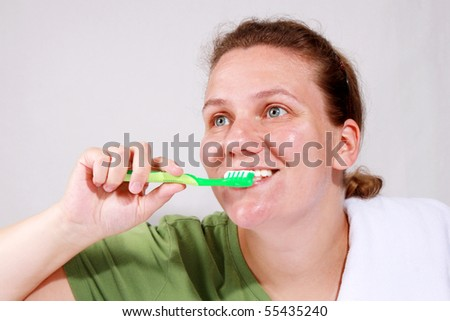 Woman brushing teeth - stock photo