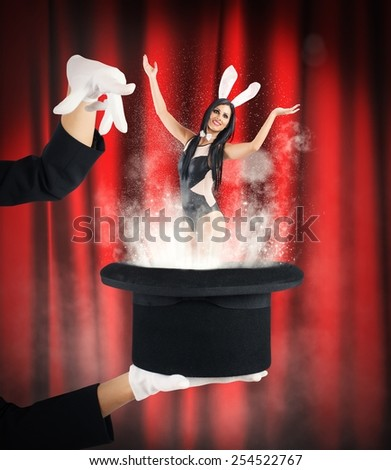 Woman bunny magically comes out of hat - stock photo
