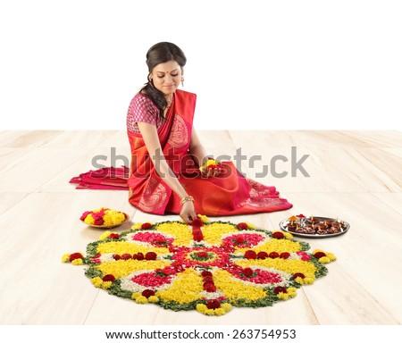 woman burning diya for Indian festival Diwali,flower rangoli decoration for Onam  - stock photo