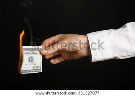 Woman burning dollars on black background - stock photo