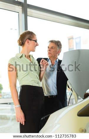 Woman buying a car in dealership looking under the hood at the engine - stock photo