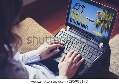 Woman buying a Last Minute flight by internet. She is typing on the laptop keyboard, looking for a sale. - stock photo
