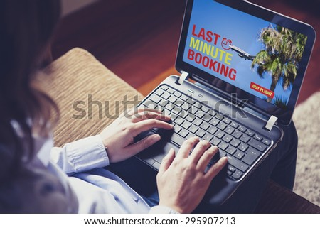 Woman buying a Last Minute Flight on the laptop. Spanish flag design on the screen text. - stock photo