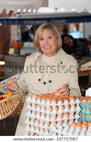Woman buying eggs at market - stock photo