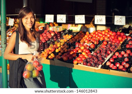 Woman buying fruits and vegetables at farmers market. Candid portrait of young woman shopping for healthy lifestyle. Multiracial Asian Caucasian female model. - stock photo