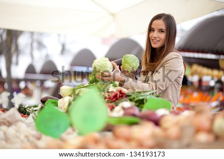 Woman buying vegetables at the market - stock photo
