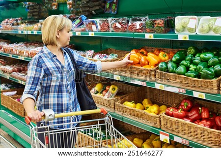 Woman buys a bell peppers in the store - stock photo