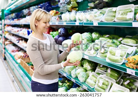 Woman buys a white cabbage in the store - stock photo