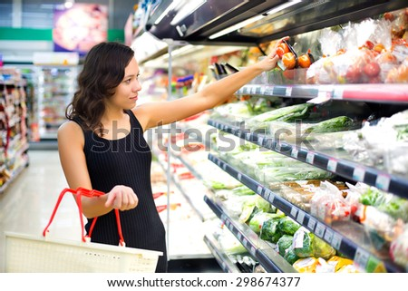 woman buys in the supermarket tomato - stock photo