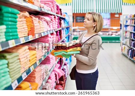 Woman buys towels in the supermarket - stock photo