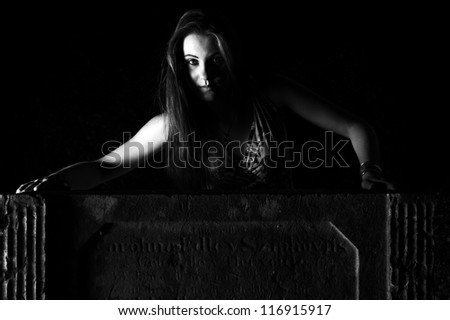 Woman by the grave - Halloween Concept - dramatic lighting - stock photo