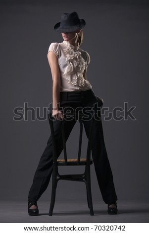 woman cabaret dancer in hat over grey background - stock photo