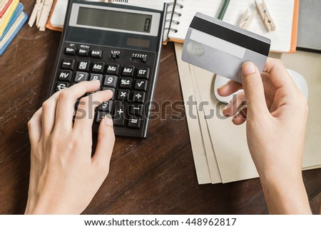 woman calculate how much cost or spending have with credit cards. Low light, selective focus on hand, can be used for e-commerce, business, technology and internet concept, Vintage tone - stock photo