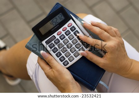 woman calculating expenses at tax time - stock photo