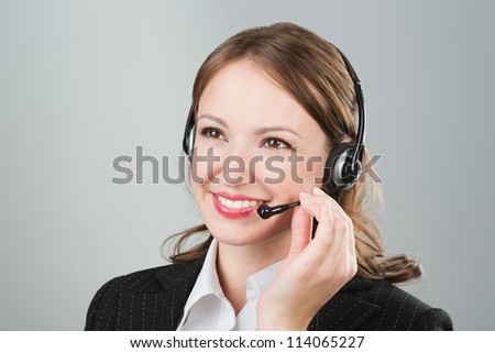 Woman call center employee speaking over the headset. Beautiful  young call center worker wearing a headset. Call center operator against grey background. Studio shot - stock photo