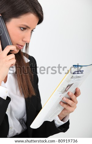 Woman calling an advert in a magazine - stock photo