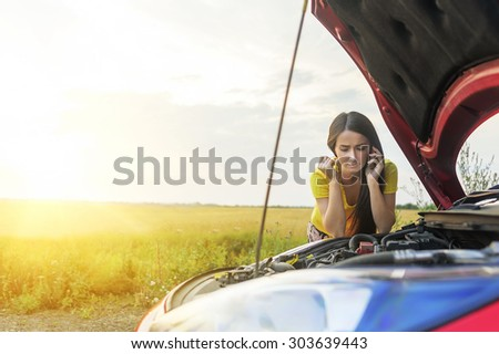 Woman calling emergency service near her broken car. - stock photo