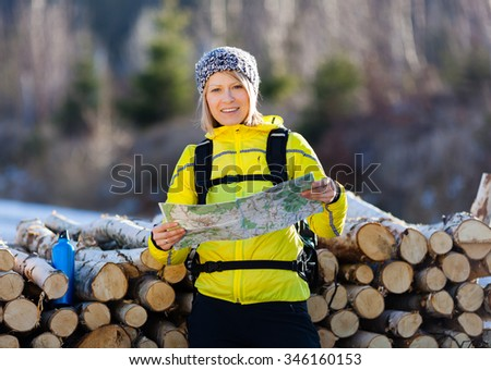 Woman camping on hiking in forest and reading map. Recreation and healthy lifestyle outdoors in nature. Beauty blond looking at camera on sunset. Inspirational winter landscape. - stock photo