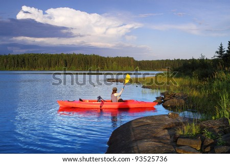 Woman canoeing in a beautiful lake at sunset - stock photo