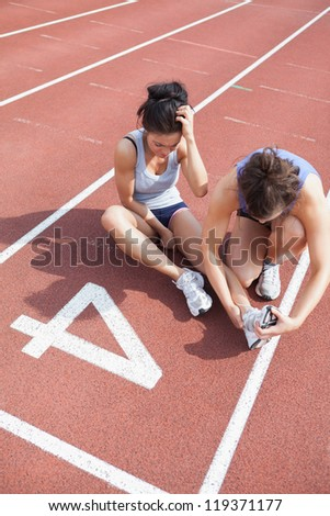 Woman caring about runner with sports injury on running track - stock photo