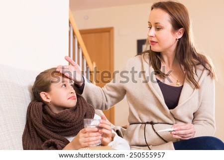 Woman caring for sick daughter who has high temperature in living room - stock photo