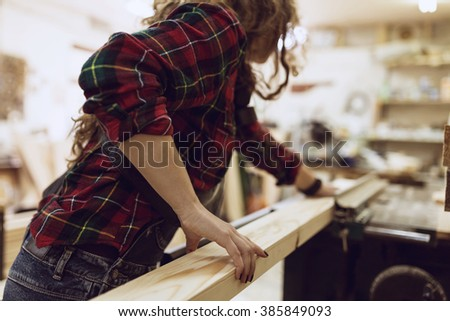 Woman Carpenter working on an electric buzz saw cutting some boards .  - stock photo