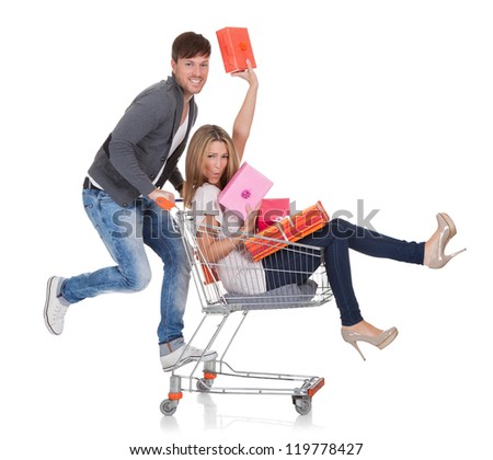 Woman carried by push cart held by man. - stock photo