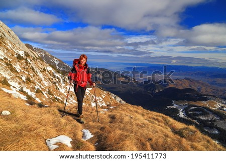 Woman carries a backpack on the side of the mountain - stock photo