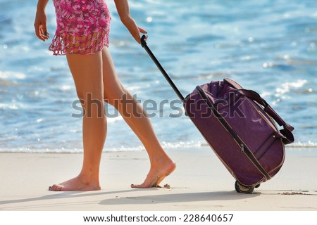 Woman carries your luggage near the blue ocean, Bali, Indonesia - stock photo