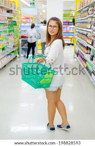 Woman carrying basket while shopping in the supermarket. - stock photo