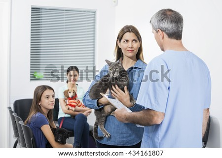 Woman Carrying Cat While Looking At Nurse In Clinic - stock photo