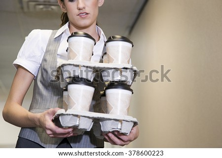 Woman carrying coffee cups - stock photo