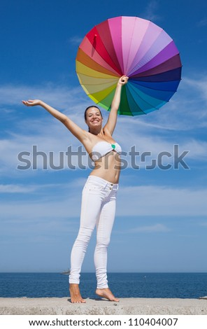 Woman carrying iridescent umbrella. Girl with iridescent umbrella on background of sky - stock photo