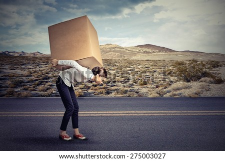 Woman carrying on her shoulders a large box  - stock photo