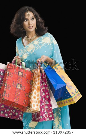 Woman carrying shopping bags and smiling - stock photo